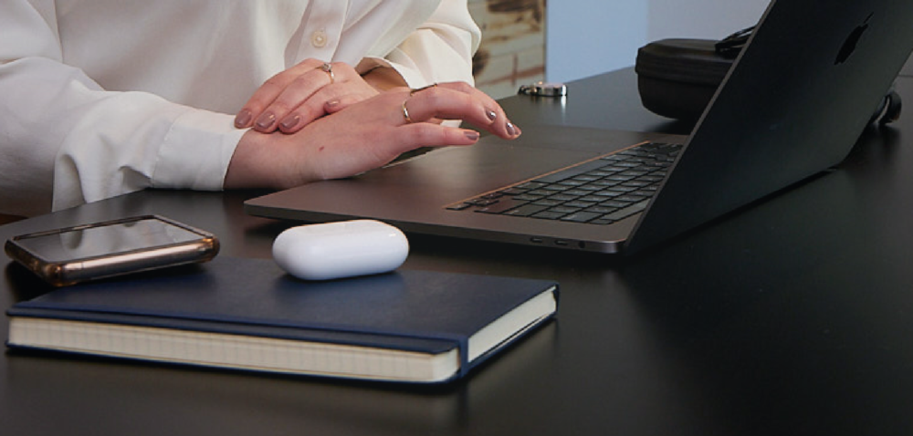 Person working on laptop at desk with notebook, Air Pods headphones, and phone.