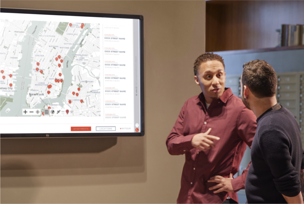 Two people conversing while interacting with large wall mounted Touch Tour screen showing software interface with location map.