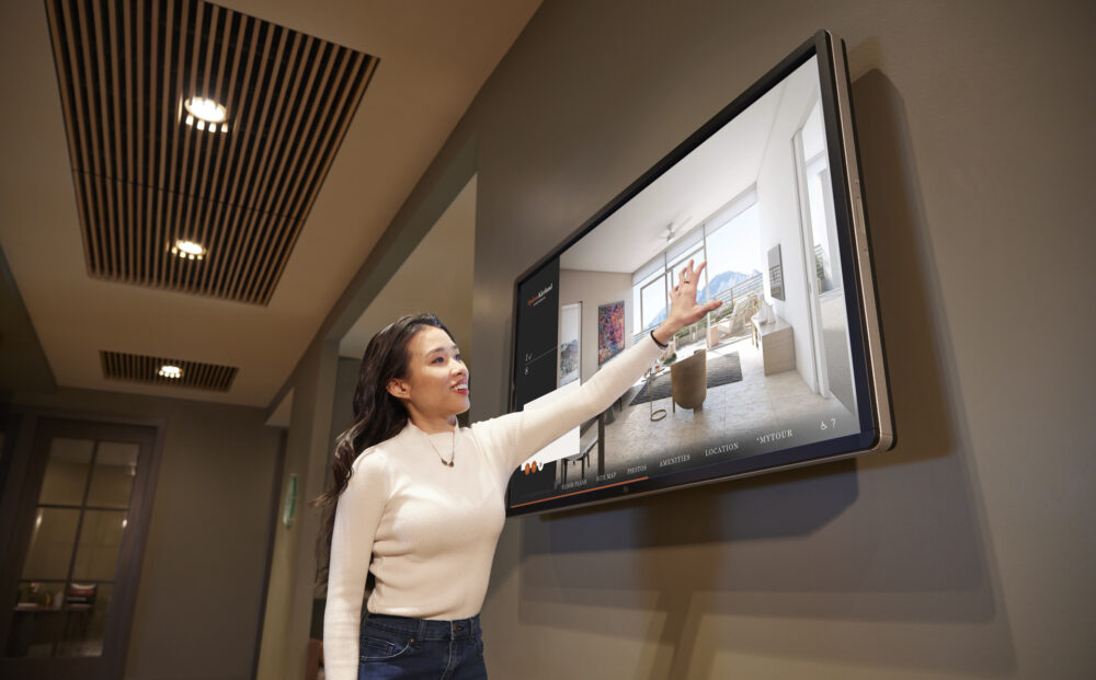 Person interacting with large wall mounted Touch Tour screen showing software interface with property photos.