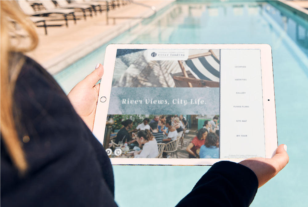 Person standing in front of sunlit pool holding iPad showing Touch Tour software interface with navigation and lifestyle photos.