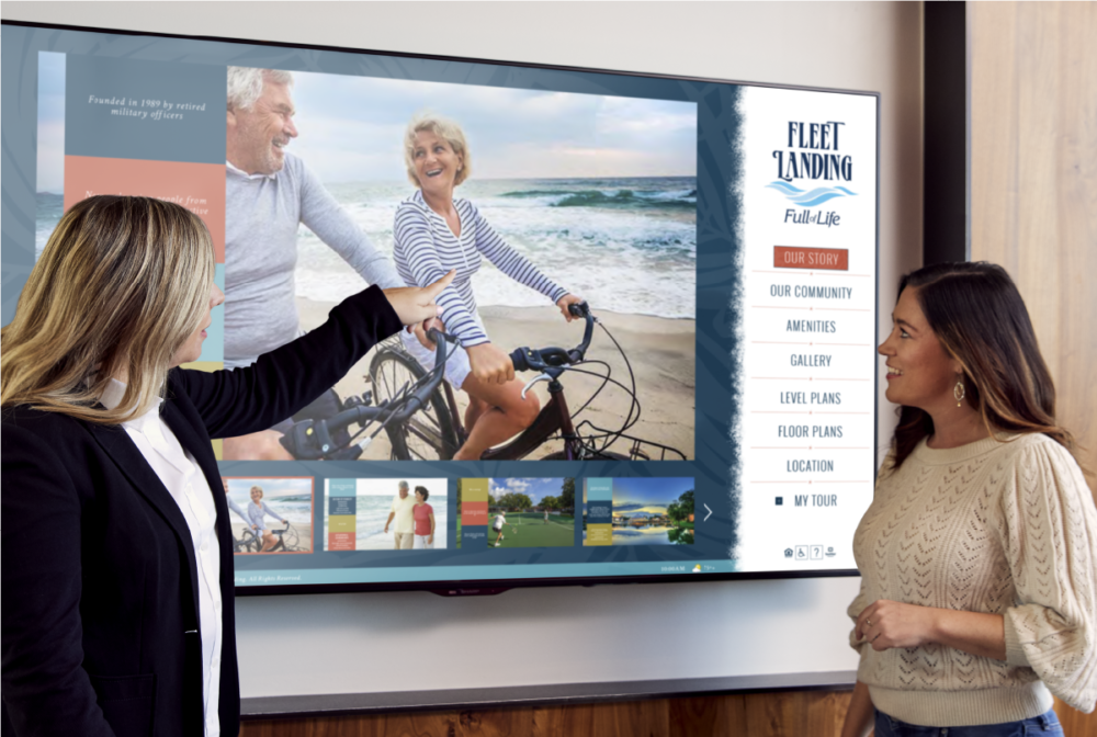 Two people in bright room interacting with large wall mounted Touch Tour screen showing software interface with lifestyle photos.